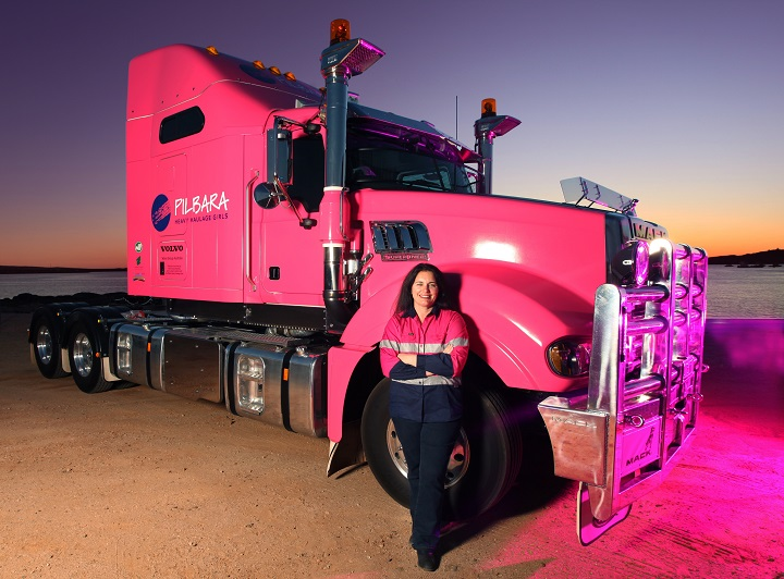 female truck driver heather jones in front of pink truck